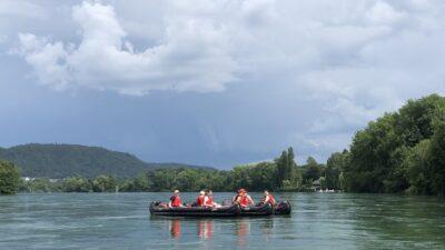 8 Personen in 4 Kanus auf dem Rhein bei bewölktem Himmel.