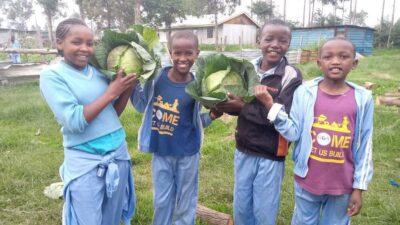 Die Kinder freuen sich über die reiche Ernte.