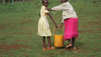 Zwei Kinder tragen einen Eimer