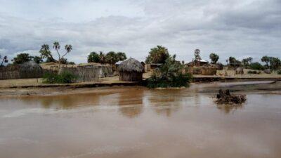 Eine Siedlung mit runden Strohhütten ist zu sehen. Diese sind auf Sand gebaut, am Horizont ragen ei paar Palmen in den Himmel. Auf dem Bildvordergrund ist stehendes Wasser zu sehen, dass bis zu den ersten Hütten reicht.