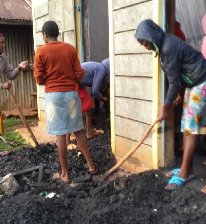 Vier Personen räumen Beschädigungen eines Brandes weg