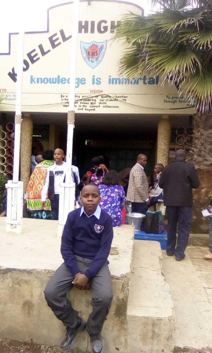 Knabe in blauer Uniform vor dem Eingang einer Schule