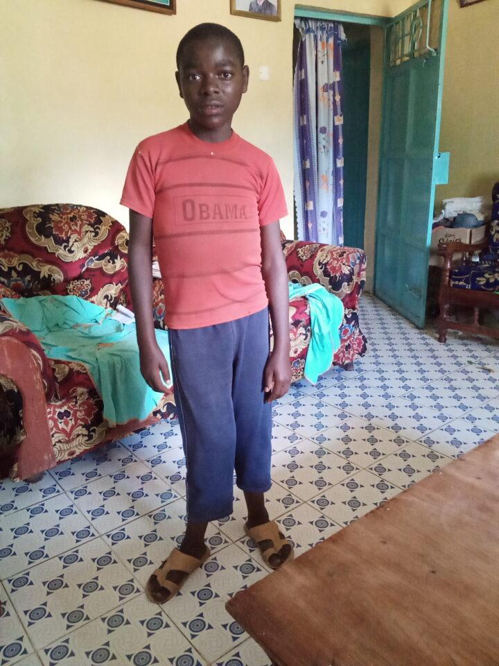 Junge in rotem Tshirt und blauer Hose steht in der Mitte eines Raums und zeigt sein deformiertes Bein