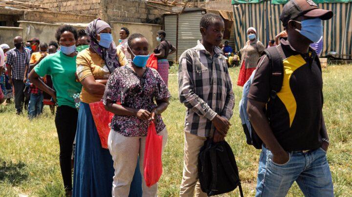 Menschen mit Mundschutz warten in einer Schlange