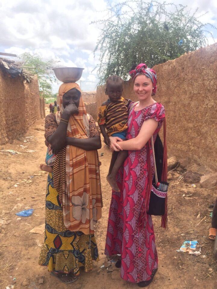 Elda Liebi in afrikanischen Gewand mit Frau und Kind vor Lehmhütten