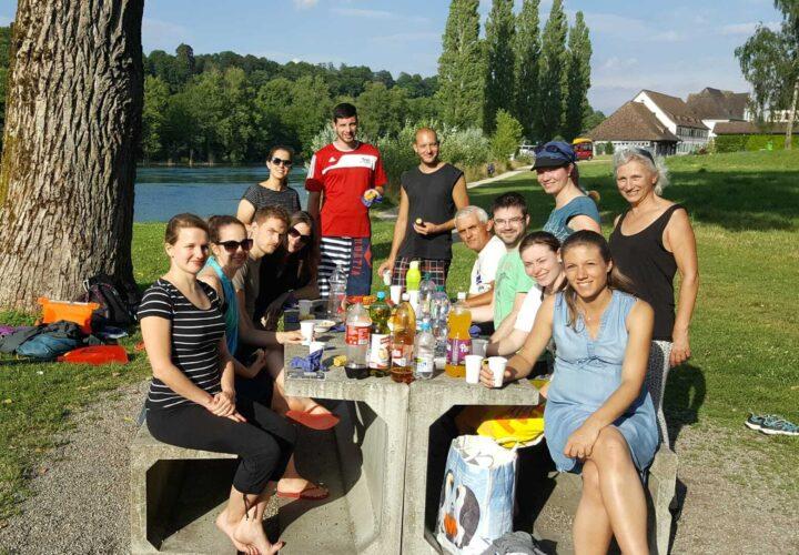 10 Personen um einen Tisch am Rheinufer.