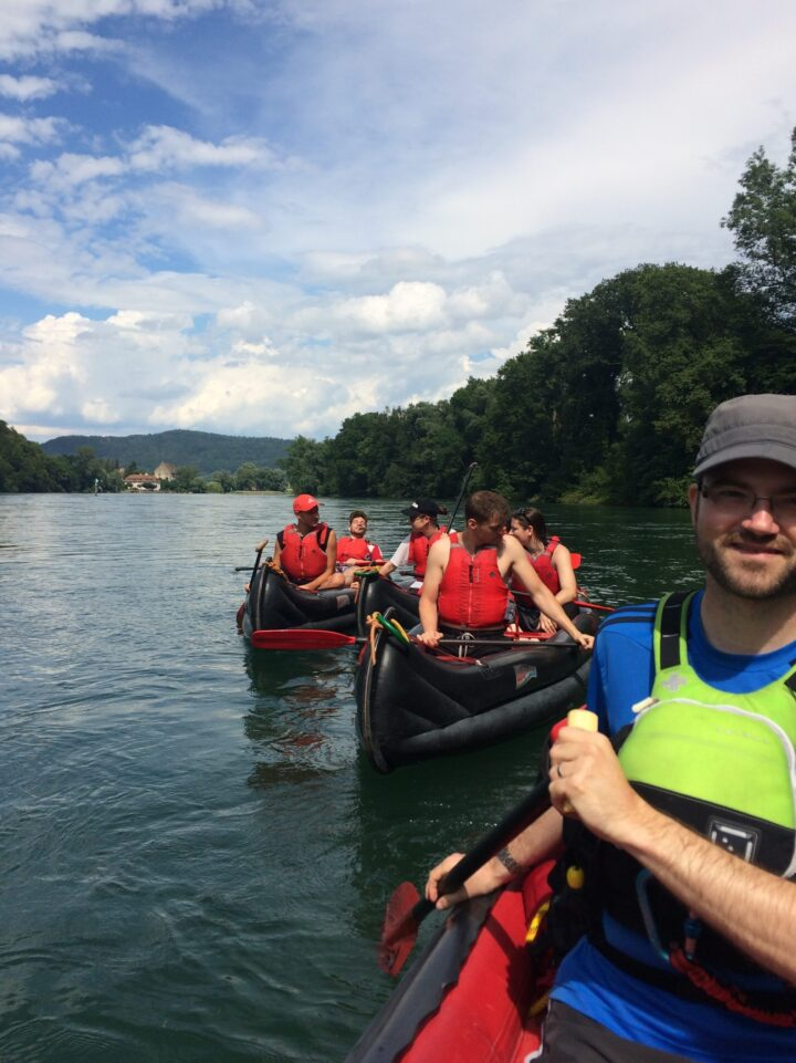Mann mit Schwimmweste auf Kanu, im Hintergrund weitere Kanus.