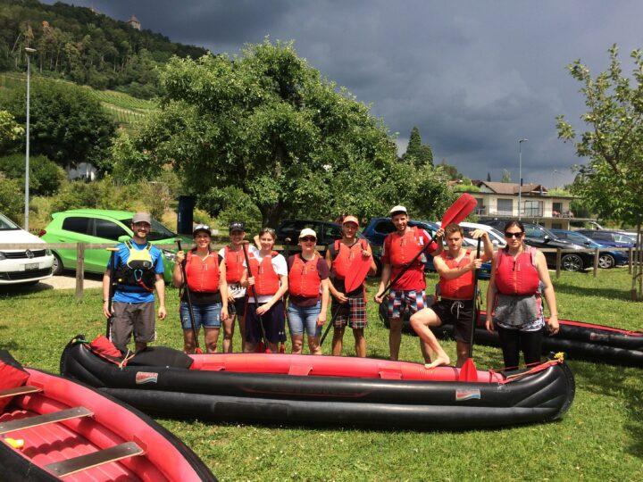 9 Personen ausgerüstet mit Schwimmweste und Paddel vor Kanu.