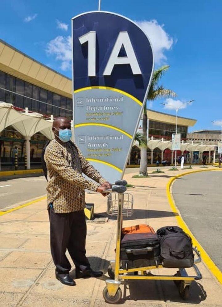 Kenianer mit Gepäcktrolley am Flughafen