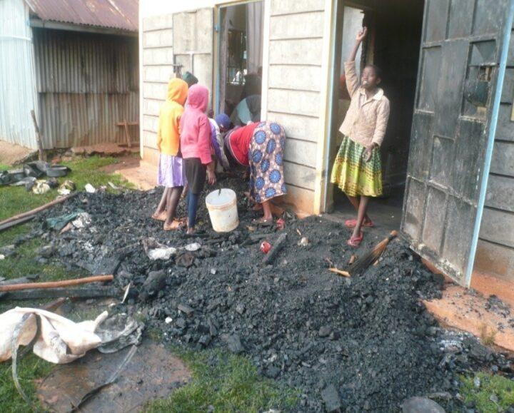 Auf dem Boden liegt eine Menge Schutt und Asche. Dahinter sind die Mauern der Küche zu sehen. Die Türe ist stark verkohlt. Ein Mädchen steht in der Türe, eine Gruppe von Mädchen steht etwas im Hintergrund und macht sich an den Überresten des Brandes zu schaffen.