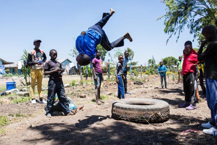 Kenianischer Junge macht einen Salto von einem alten Lastwagenpneu