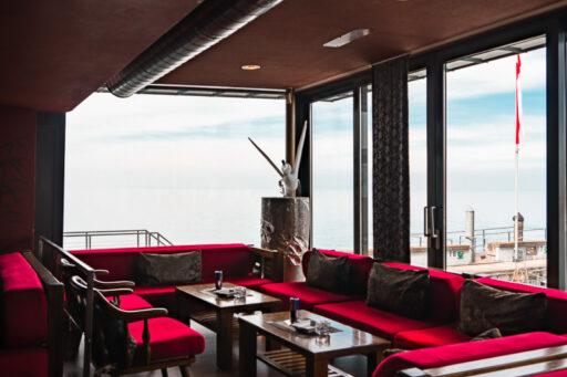 Lokal mit roten Sofas und Seesicht im Hintergrund