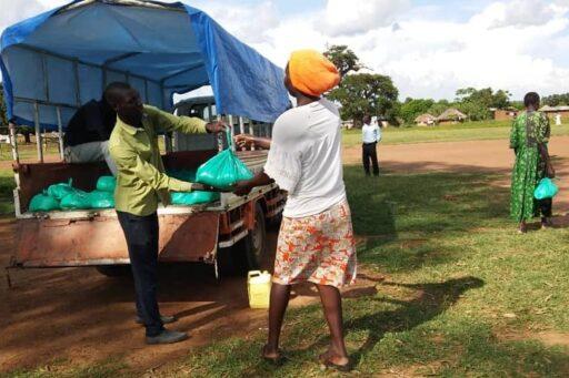 Mann lädt Essenspaket vom Lastwagen und übergibt es einer Frau