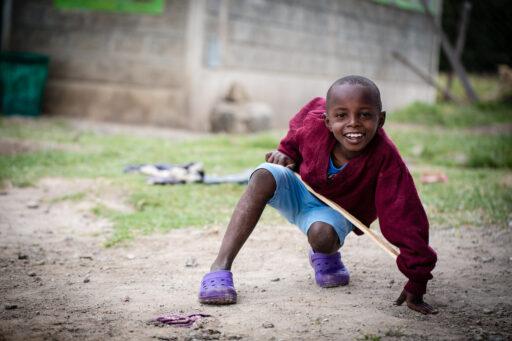 Kauernder kenianischer Junge in rotem Pullover, hellblauen kurzen Hosen und violetten Kroks