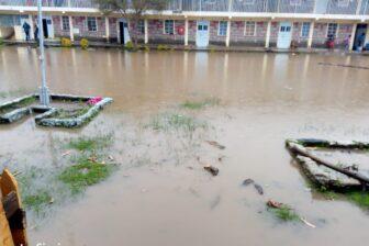 Überschwemmter Platz zwischen den Gebäuden von Tumaini