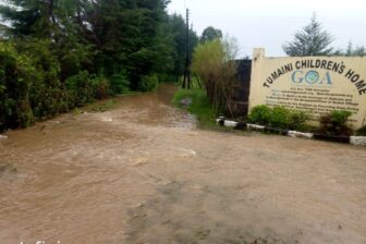 Überflutete Strasse vor dem Tor des Waisenhauses Tumaini
