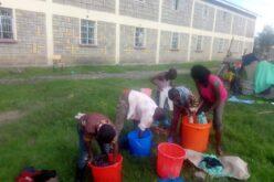 Die Sozialarbeiterin zeigt dein kleinsten Kindern, wie man seine Wäsche richtig wäscht.