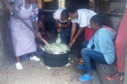 Die Köchin zeigt den Kindern, wie die traditionelle Speise Mukimo (Kartoffelstock) zubereitet wird.