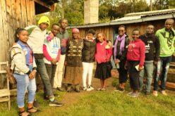 Ein Gruppenfoto. Darauf sind elf Personen zu sehen, die meisten davon Jugendliche. In der Bildmitte ist eine ältere Dame zu sehen. Im Hintergrund sind zwei Holzhütten im Ansatz erkennbar.