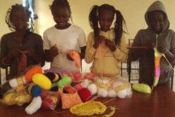 Vier Kinder stehen hinter einem Tisch. Auf dem Tisch liegt ein ganzer Berg a Wolle und Garn in unterschiedlichen Farben.