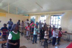 Blick in einen grossen Raum mit mehreren Bankreihen. Ein Schar von etwa 20 Kindern steht in den Reihen, teils mit erhobenen Armen.