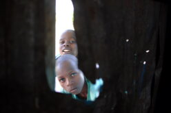 Kind schaut durch Loch in Wellblech