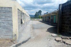 Zu beiden Seiten des Bildes liegt ein Flachdachgebäude. Dazwischen liegt ein frisch betonierter Vorplatz.