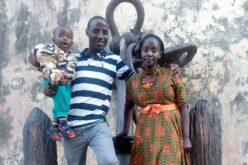 Ein kenianisches Paar, sie steht links und trägt ein oker-oranges Kleid. Er steht links in einem blau weiss gestreiften Polo-Shirt. Auf seinem Arm trägt er ein Kind.