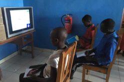 Drei Kinder auf Holzstühlen mit ihren Heftern auf dem Schoss sitzen vor einem Fernseher.