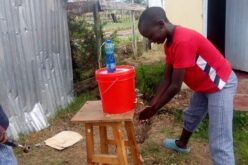 Holzhocker mit einem roten Eimer darauf. Darauf wiederum blaue PET-Flasche. Junge mit rotem T-Shirt wäscht sich daruntert die Hände.