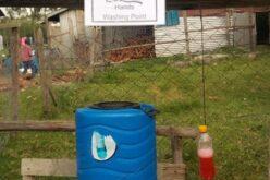 Blaues Fass, daneben PET-Flasche mit roter Flüssigkeit, darüber Zettel mit Aufschrift: Hands Washing Point