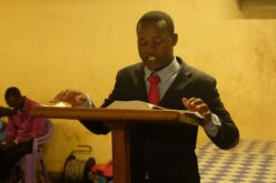 Ein Jugendlicher steht hinter einem Rednerpult. Darauf liegt die geöffnete Bibel. Der Jugendliche ist in einem blauen Anzug gekleidet, dazu trägt er eine rote Krawatte.