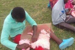 Kind sitzt auf dem Grasboden. Auf dem Schoss liegt ein kleiner, rosaner Teppich, an dem es gerade knöpft.