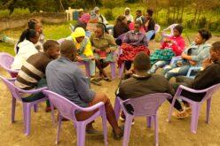 Eine Gruppe von elf Jugendlichen sitzt in einem Kreis. Die Personen sitzen auf lila Plastikstühlen.