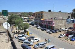 Blick über Naivasha: Strasse und geparkte Autos, steinerne Gebäude, Werbetafel, einige staubige Nebenstrassen