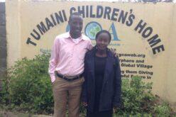"""Kenianisches Paar. Er steht links (rosa Hemd, beige Hose), sie rechts (schwarzes Kleid, dunkelblaucer Mantel. Im Hintergrund ist auf einer Wand der Schriftzug """"Tumaini Children's Home"""" zu erkennen."""