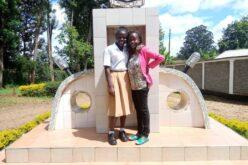 Zwei kenianische Frauen. Die linke in Schuluniform (weisse Bluse, hellbrauner Jupe), die Rechte mit pinkem Oberteil und schwarzer Hose. Die Frau in Schuluniform legt ihren Arm um die Schulter der zweiten Frau