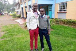 Ein kenianischer Mann mit weissem Jacket und roter Hose steht links. Recht steht ein kenianischer Jugendlicher in Schuluniform (grauer Pullover, dunkelblaue Hose). Die beiden haben sich die Arme um die Schulter gelegt