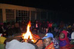 In der Bildmitte ist ein grosses Feuer z sehen, darum herum haben sich viele Kinder versammelt. Aufgrund der Dunkelheit lassen sich aber nur diejenigen im Vordergrund deutlich erkennen.
