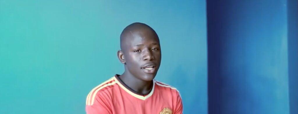 Junge mit rotem Tshirt sitzt vor blauer Wand