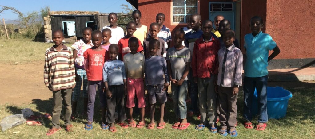 20 Kinder stehen vor dem Waisenhaus Beat the Drum