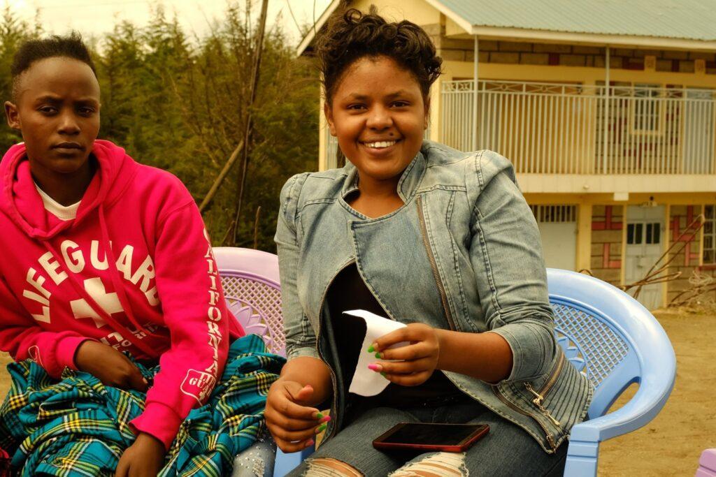 In der Bildmitte sitzt eine jugen Frau. Sie strahlt in die Kamera. In einer Hand hält sie einen Zettel, auf ihrem Schoss liegt ein Handy. Links daneben ist eine weitere junge Frau zu sehen, die einen etwas kritischen Blick hat.