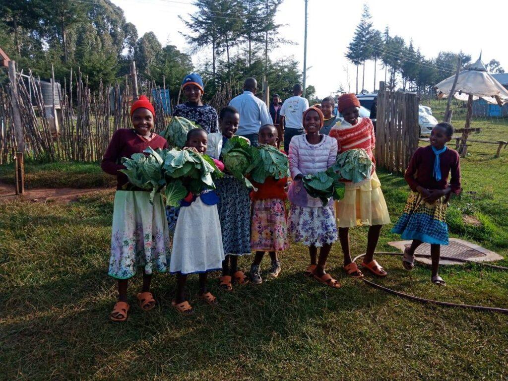 Eine Gruppe von Mädchen steht strahlend zusammen. In den Händen hält eine jede ein Weisskohl.