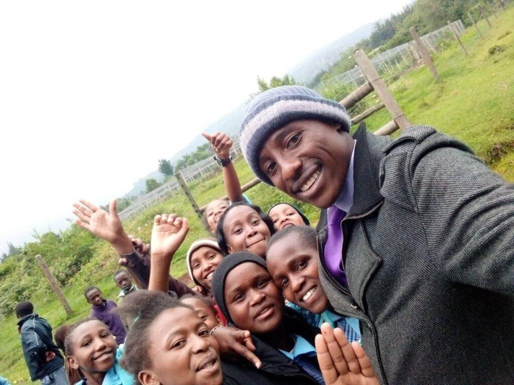 Ein Mann mit Mütze und grauem Mantel steht rechts. Links daneben sind kenianische Kinder zu sehen. Alle lächeln, auch ein paar Hände werden in die Höhe gehalten