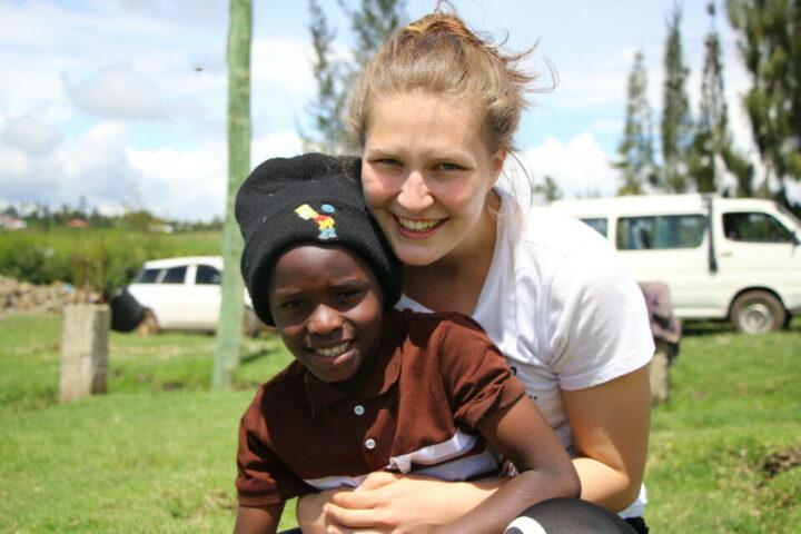 Schweizer Volontärin hält kenianisches Kind mit schwarzer Mütze