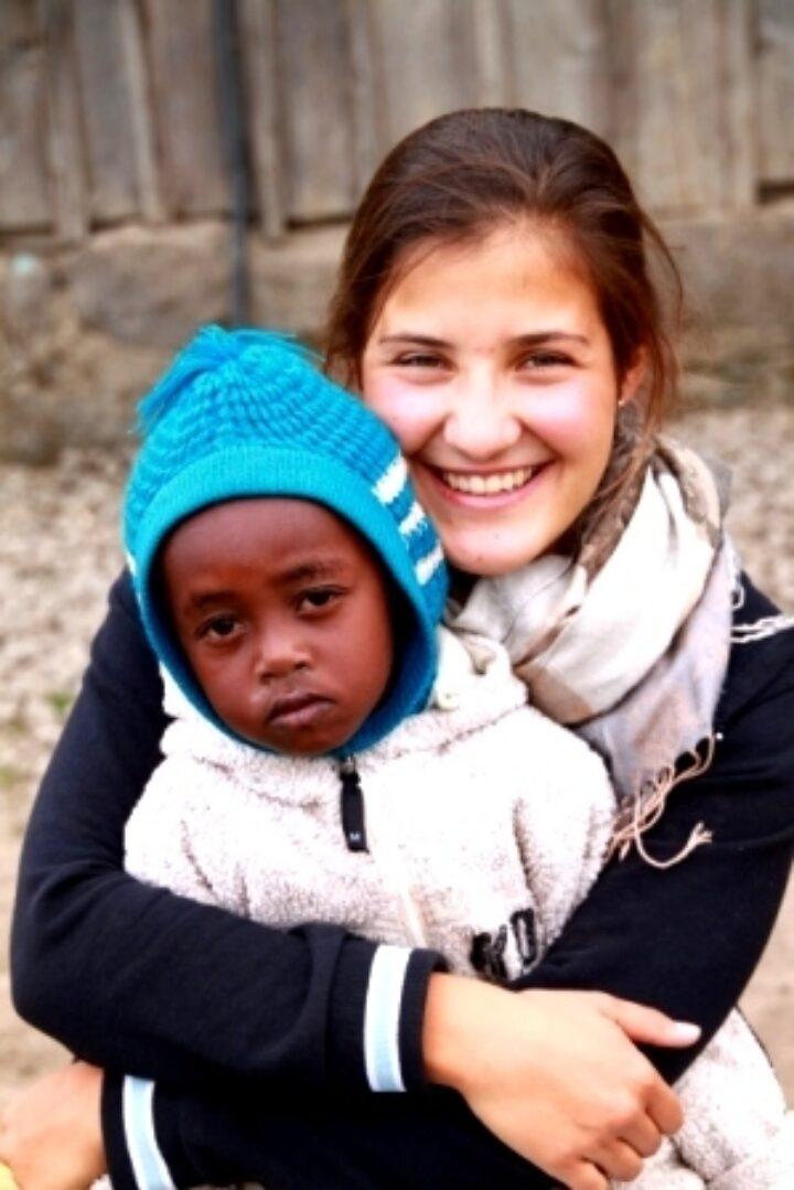 Schweizer Volontärin hält kenianisches Kleinkind mit blauer Mütze