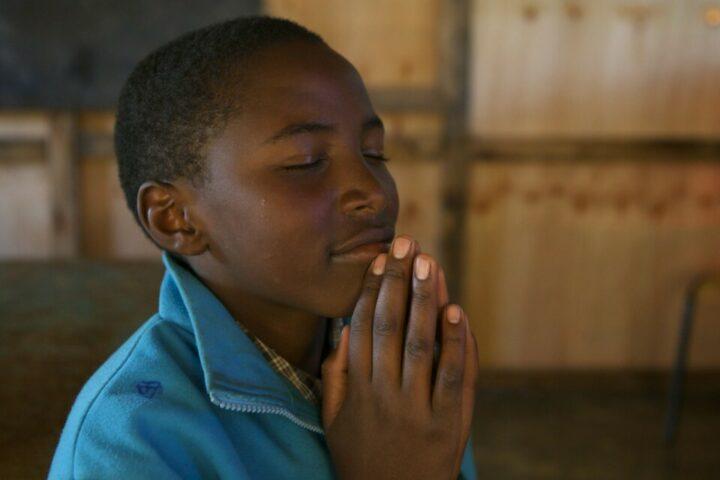 Kenianisches Kind mit geschlossenen Augen und gefalteten Händen am Beten.