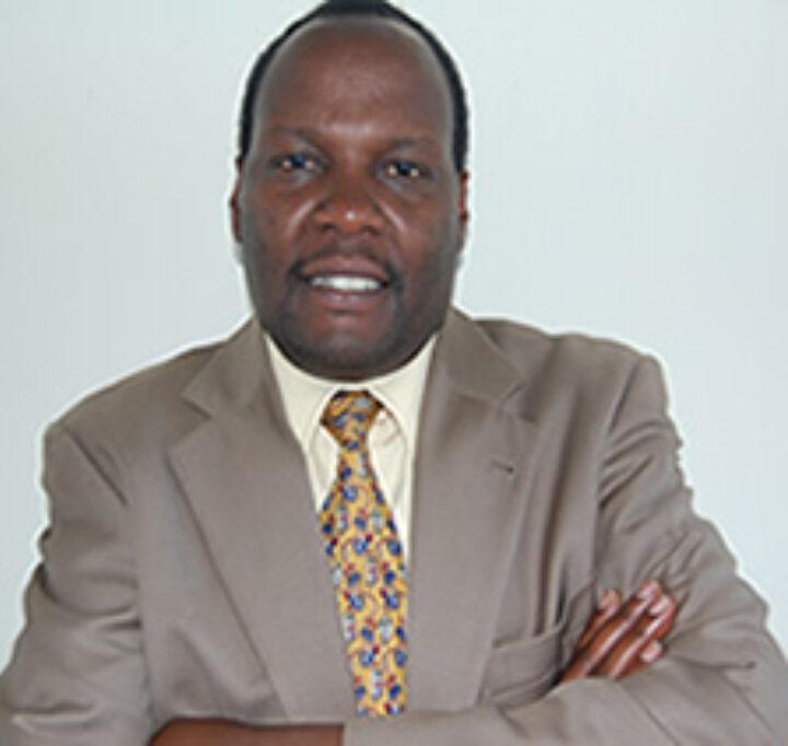 Kenianischer Mann in grauem Anzug mit gelb-gemusterter Krawatte