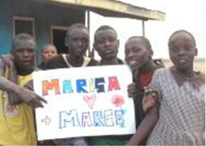 5 kenianische Kindern halten ein Glückwunschschild hoch