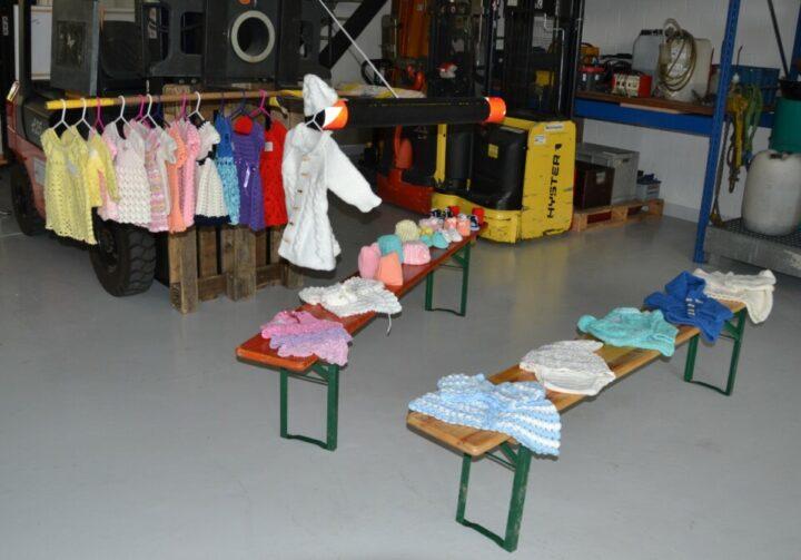Fabrikhalle mit handgemachten Stricksachen ausgelegt auf Klappbänken